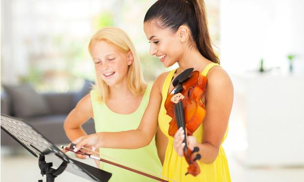 2 female students having a violin lesson.