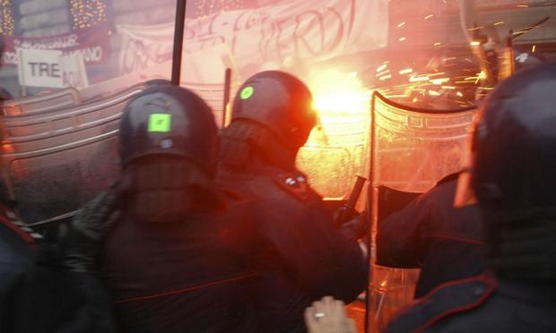 Demonstrators (back), protesting against the Italian government's austerity budget cuts, clash with riot policemen outside La Scala