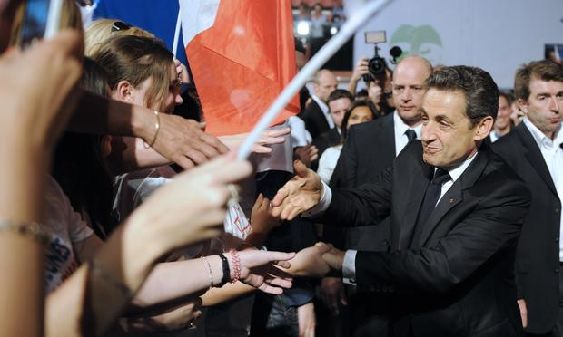 France's incumbent president and Union for a Popular Movement (UMP) party candidate for the French 2012 presidential election Nicolas Sarkozy (R) shakes hands with supporters after delivering a speech