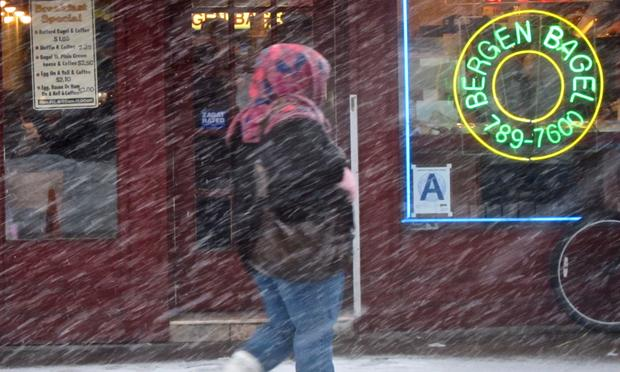 Neon invites New Yorkers in for a hot bagel in Brooklyn as the snow falls.