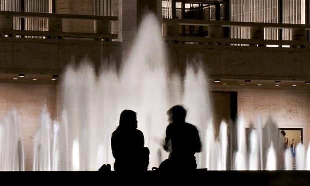 silhouettes of a couple of people in front of the Lincoln Center fountain