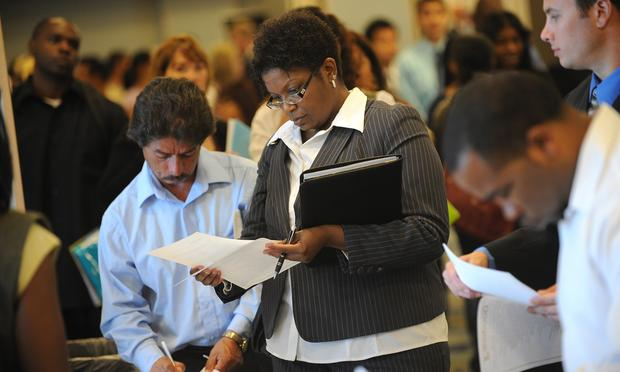 Job seekers look for employment at a job fair in Los Angeles on September 20, 2010