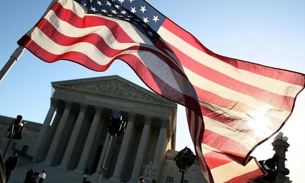 A person carries an American flag while marching in favor of the Patient Protection and Affordable Care Act in front of the U.S. Supreme Court on March 26, 2012 in Washington, DC. (Getty)