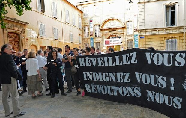 French artists and entertainment workers, known in France as 'Intermittents du spectacle', holding a banner reading 'Wake up, be indignant, let's revolt' demonstrate on July 3, 2014 in Aix-en-Provence
