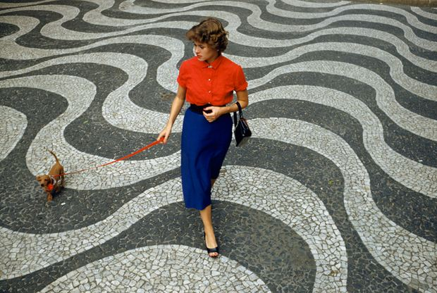 A woman walks a dachshund across pavement with undulating wave patterns in Rio de Janeiro, Brazil, March 1955. (Photograph by Charles Allmon, National Geographic)