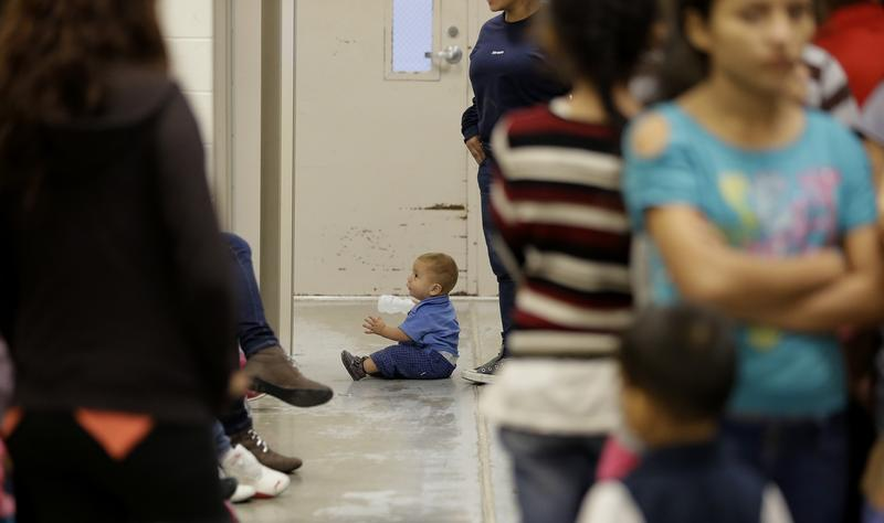A toddler sits on the floor with other detainees at a U.S. Customs and Border Protection processing facility, on June 18, 2014, in Brownsville,Texas.