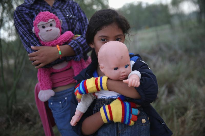 Salvadorian immigrant Stefany Marjorie, 8, holds her doll Rodrigo after crossing the Rio Grande from Mexico into the United States with her family on July 24, 2014 near Mission, Texas.