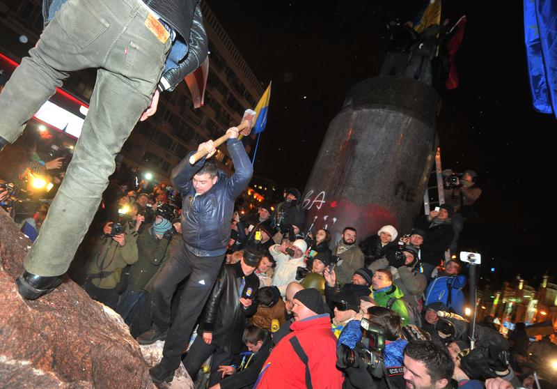 A protester breaks apart a statue of Lenin at a monument in his honor after it was pulled down during a mass rally called 'The March of a Million' in Kiev's Independence Square on December 8, 2013.