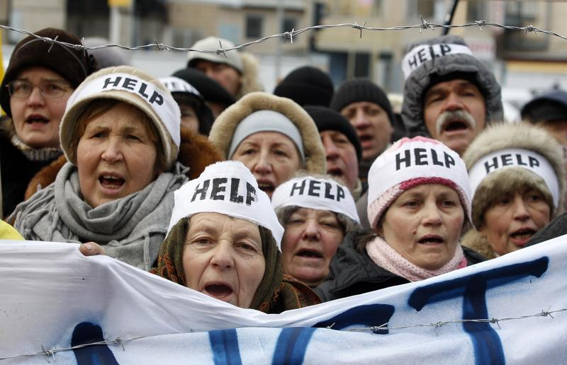 Protesters wearing headbands reading 'Help' shout slogans during an action entitled 'Impose sanctions—stop the violence' in front of the European Union delegation in Ukraine in Kiev of Jan. 20, 2014.