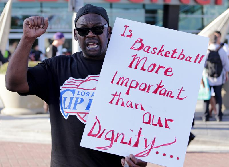 A man holds a sign during a protest against racist comments made by L.A. Clippers owner Donald Sterling outside Staples Center before a playoff game on April 29, 2014 in Los Angeles, California.