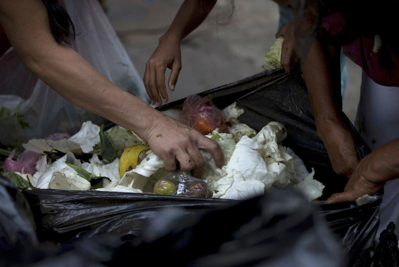 In this June 2, 2016 photo, people search a garbage bag for vegetables and fruit outside a supermarket in downtown Caracas, Venezuela.