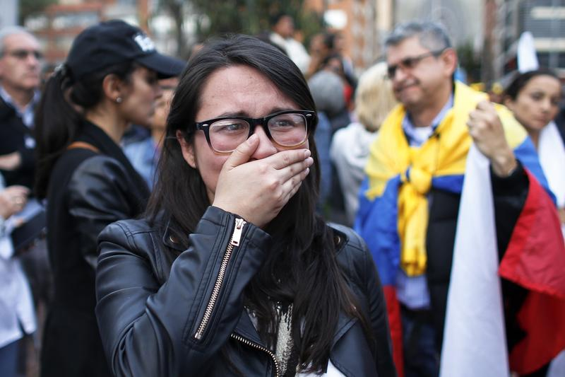 A supporter of the FARC peace deal cries as she watches the results of a referendum to decide whether or not to support the deal in Bogota, Colombia, Sunday, Oct. 2, 2016.