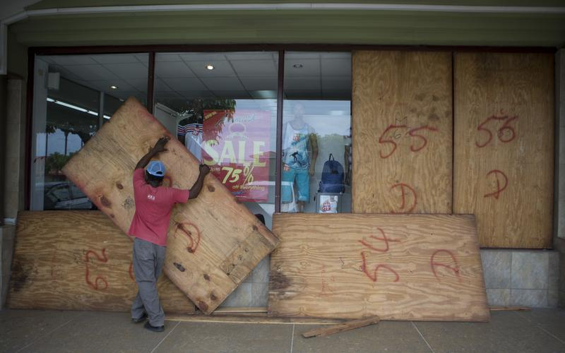 A worker removes plywood from shop windows after the passing of Hurricane Matthew in Kingston, Jamaica, Tuesday, Oct. 4, 2016.