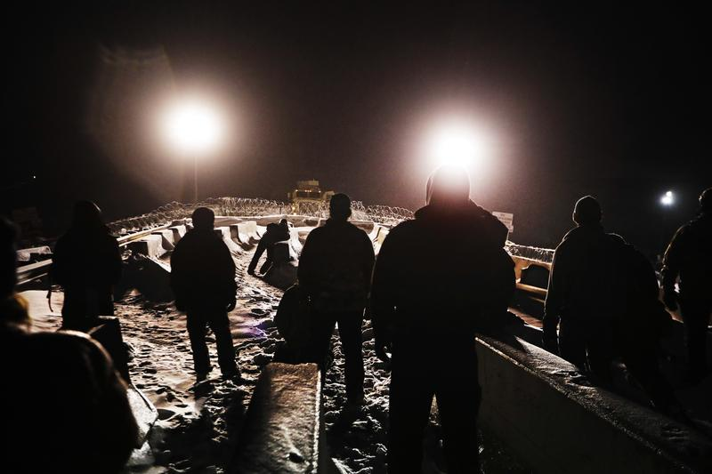 In this Thursday, Dec. 1, 2016 photo, military veterans walk onto a closed bridge to protest across from police protecting the Dakota Access oil pipeline site in Cannon Ball, N.D.