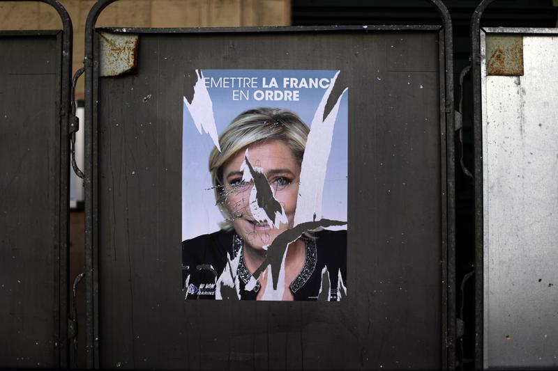 A torn poster showing a portrait of far-right leader and candidate for the 2017 French presidential election Marine Le Pen is seen outside at a polling station in Paris, Sunday, April 23, 2017.