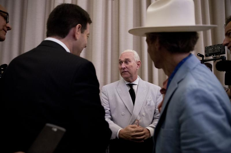 Roger Stone, center, speaks to reporters before the start of a campaign event for Republican presidential candidate Donald Trump, July 16, 2016.