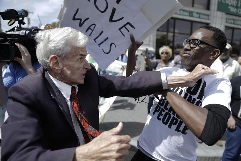 Jerry Lambert, left, a supporter of Republican presidential candidate Donald Trump, and Asa Khalif, a Black Lives Matter supporter, scuffle, after Khalif took Lambert's sign during a protest.