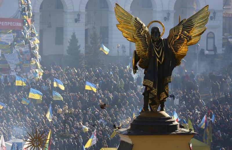 The Archangel Michael statue towers over pro-European Union activists during a rally in Independence Square in Kiev, Ukraine, Saturday, Dec. 14, 2013.
