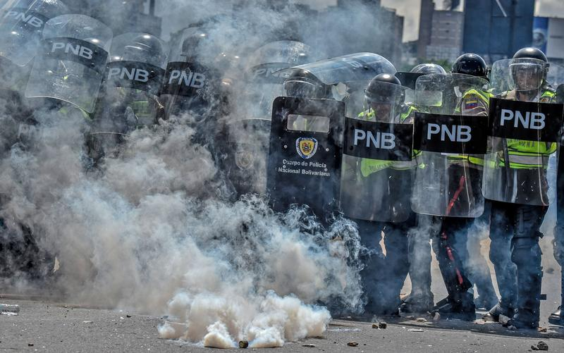 Riot police face opposition activists marching in Caracas, on September 1, 2016.