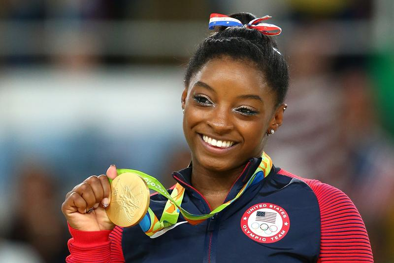 Gold medalist Simone Biles of the United States celebrates on the podium at the medal ceremony for the Women's Floor on Day 11 of the Rio 2016 Olympic Games.