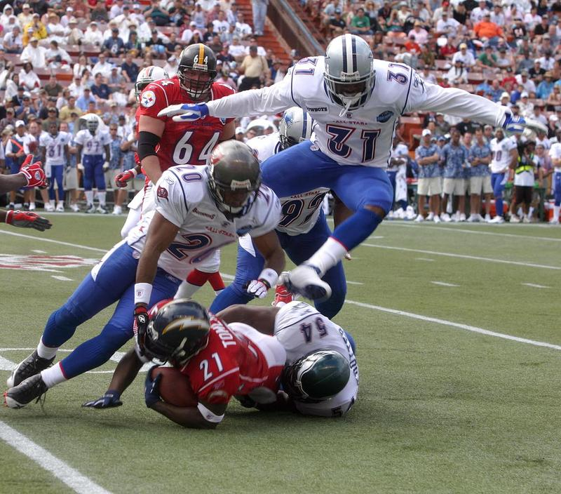 NFC defensive backs Ronde Barber and Roy Williams along with linebacker Jeremiah Trotter gang tackle AFC running back Ladainian Tomlinson during the 2006 Pro Bowl in Hawaii.