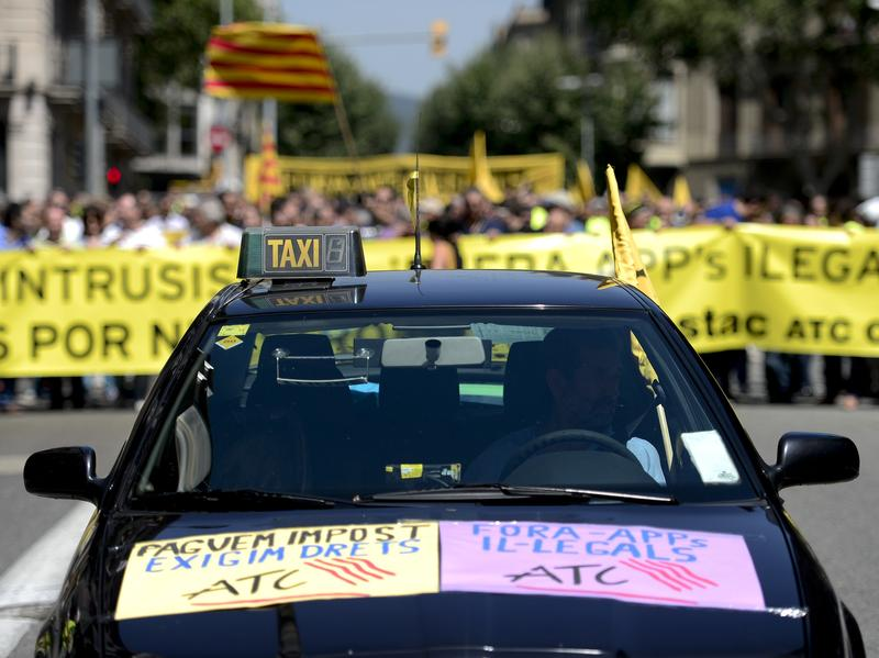 A taxi precedes demonstrators during a protest against Uber in Barcelona on Wednesday. A conventional taxi license in Spain can cost 137,000 euros ($185,400), making competition from services like Uber a major financial issue.