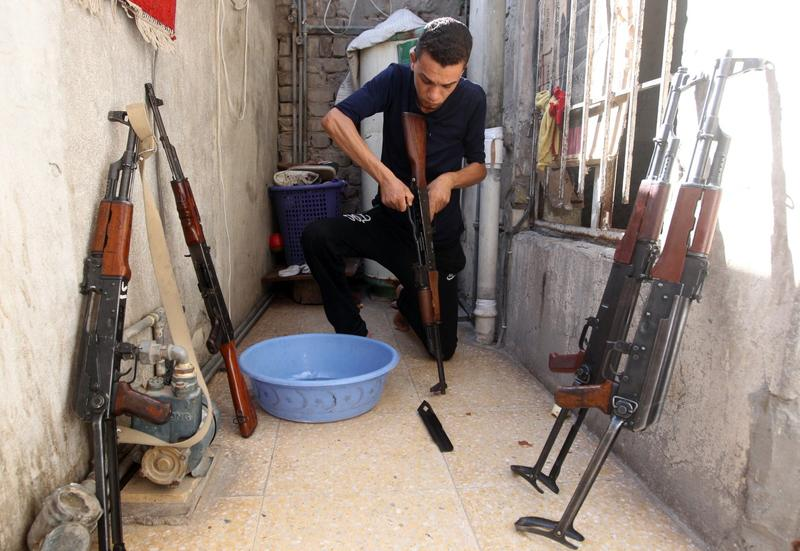 An Iraqi Shiite man cleans weapons as he gets ready to defend his Sadr City district in case of an attack by Sunni extremists, on June 13, 2014 in Baghdad. (Ahmad al-Rubaye/AFP/Getty Images)