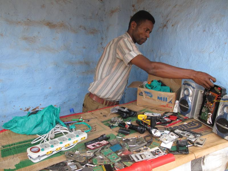Mohammed Osman Ali, a refugee in Uganda, sorts through spare parts for his video game arcade business.