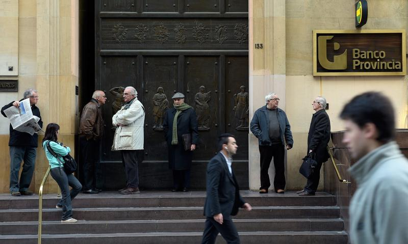 Retired citizens await the opening of the Banco Provincia bank headquarters in the financial district near Plaza de Mayo square to collect their pensions, in Buenos Aires on July 30, 2014. Last-ditch talks aimed at averting Argentina's second default in 13 years were to resume Wednesday in New York, after Tuesday's marathon session failed to reach a deal. (Daniel Garcia/AFP/Getty Images)