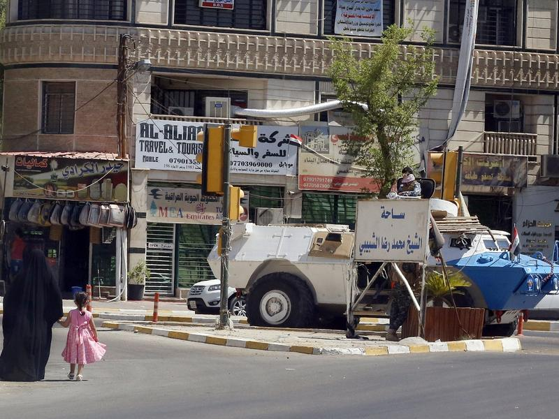 An Iraqi woman and child walk toward an Iraqi security armored personnel carrier on a Baghdad street, a sign of the political showdown between incumbent Prime Minister Nouri al-Maliki and those calling for his tenure to end.