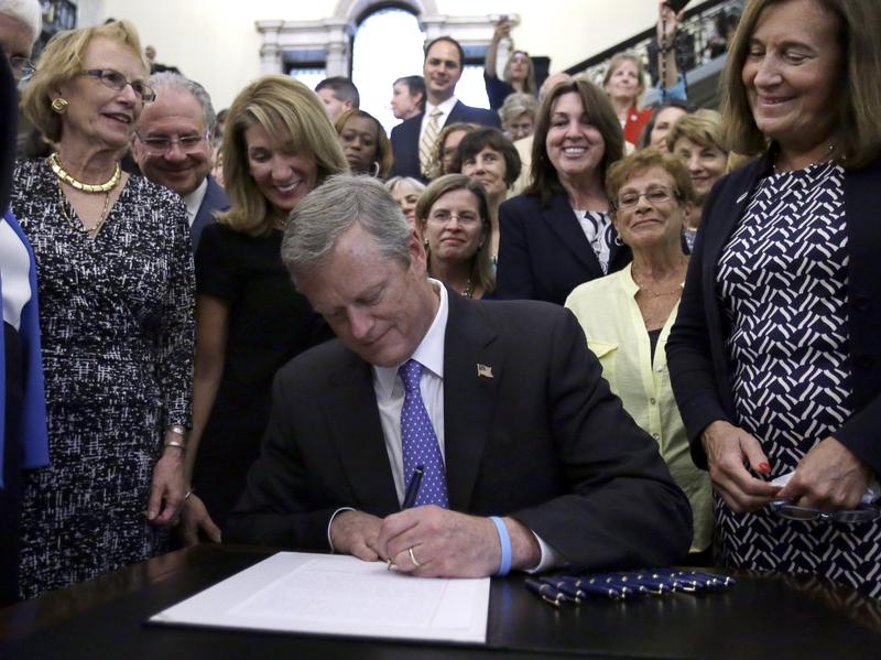 Massachusetts Gov. Charlie Baker signs a pay equity act into law at the Massachusetts State House on Monday in Boston.