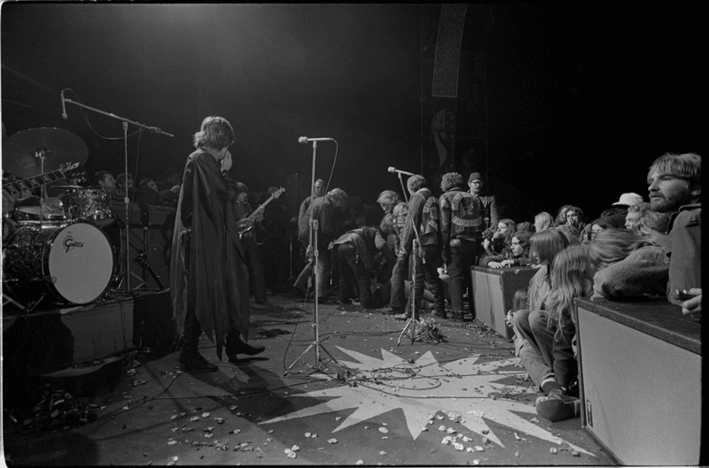 Mick Jagger covers his face as the body of Meredith Hunter is pushed from the stage at the Altamont Free Concert at Altamont Speedway, California on Dec. 6, 1969. Hunter was stabbed to death, allegedly by a Hells Angel. (Courtesy of Beth Bagby)