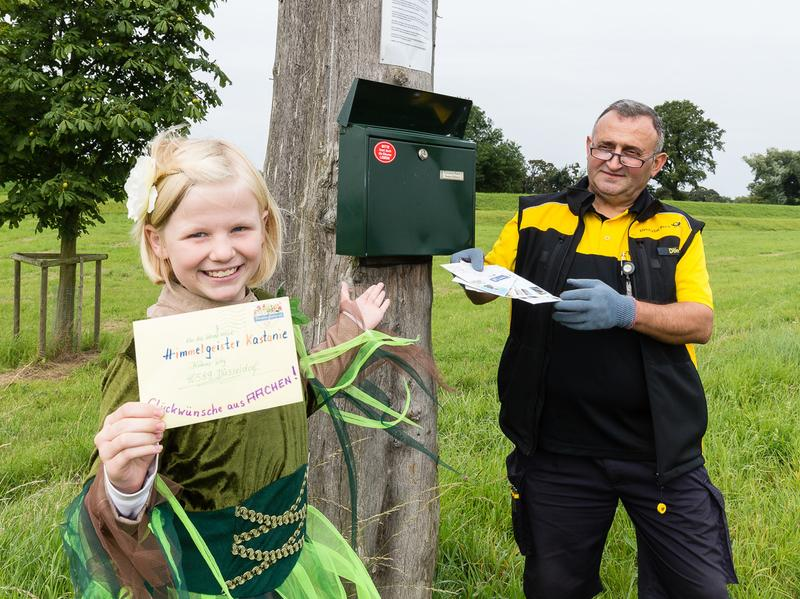 Tree intern, Leni Classen (left), responds to letters sent to a chestnut tree in Dusseldorf, Germany. A postal worker from Deutsche Post (right) delivers mail to the tree's mailbox. The tree, which is planted in a nature reserve, has its own address and people often write to it for advice or to ask questions.