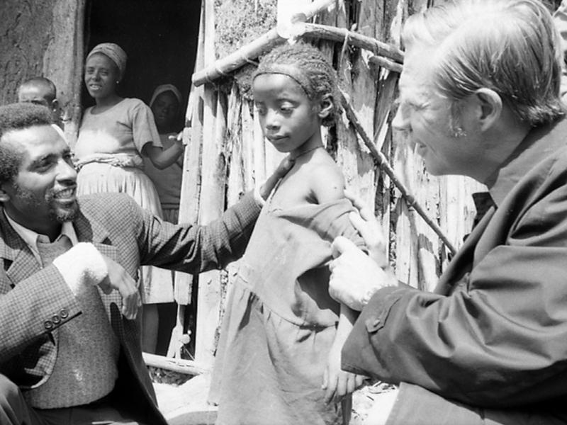 Dr. Donald A. Henderson (right), who led the World Health Organization effort to eradicate smallpox, examines a child's vaccination scar in Ethiopia.