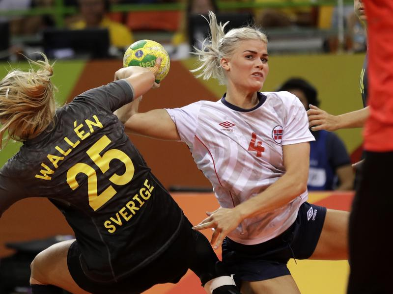 Norway's Veronica Kristiansen is challenged by Sweden's Angelica Wallen (left) as she tries to score during the women's quarterfinal handball match between Norway and Sweden on Tuesday.