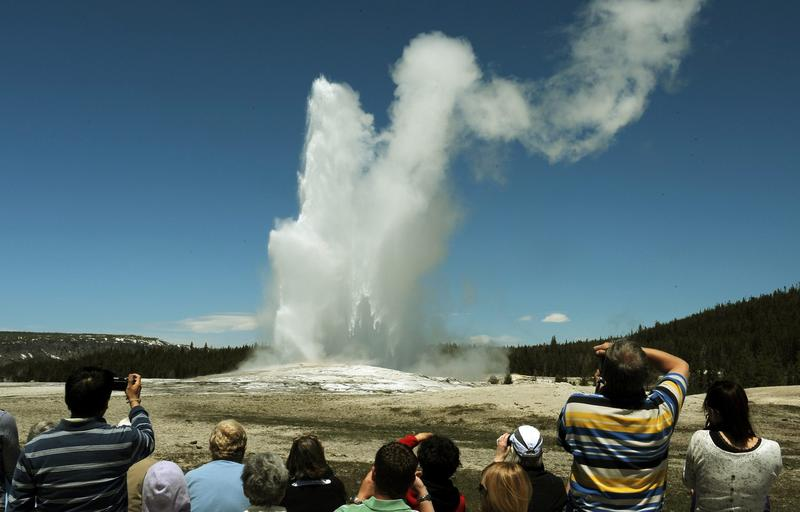 """Tourists watch the """"Old Faithful"""" geyser, which erupts on average every 90 minutes, at Yellowstone National Park in Wyoming on June 1, 2011. (Mark Ralston/AFP/Getty Images)"""