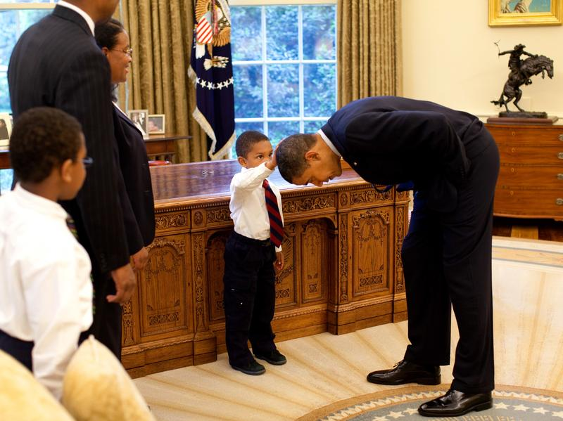 President Barack Obama bends over so the son of a White House staff member can pat his head during a visit to the Oval Office on May 8, 2009.