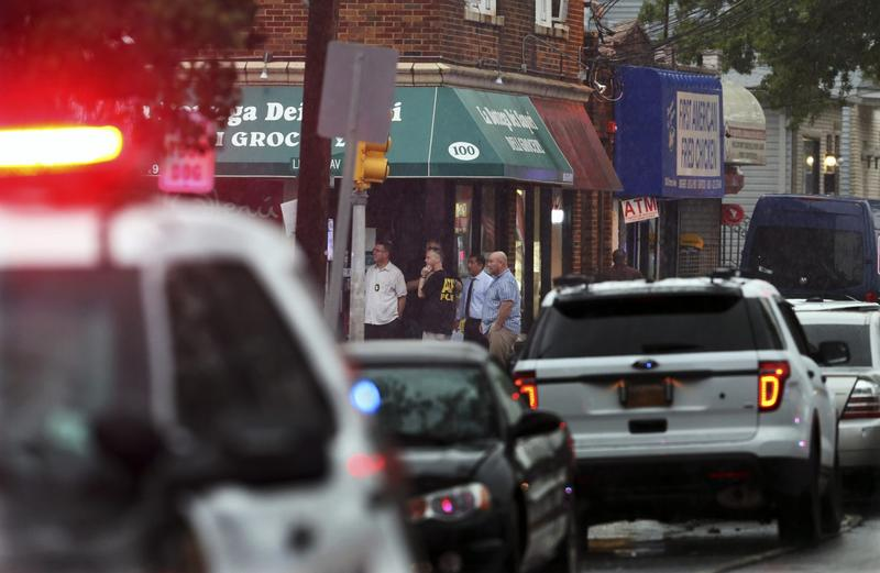 Police and officials gather in the doorway of a building early Monday, Sept. 19, 2016, in Elizabeth, N.J. A suspicious device found in a trash can near a train station exploded early Monday as a bomb squad was attempting to disarm it with a robot, officials said. (Mel Evans/AP)