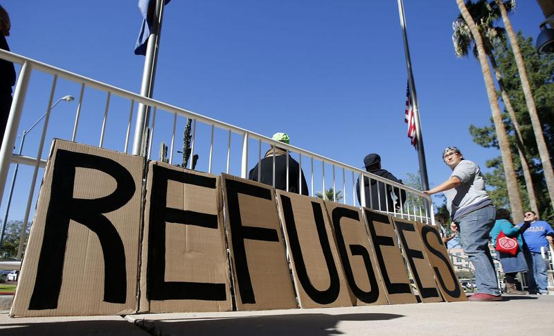 A sign welcoming Syrian refugees is placed at the entrance to the office of the Arizona governor during a rally at the Arizona Capitol Tuesday, Nov. 17, 2015, in Phoenix. The Syrian civil war, which has produced nearly 5 million refugees and internally displaced millions more, drove Bassam Al Abbas and his family from their home. They eventually settled in Austin, Texas. (Ross D. Franklin/AP)