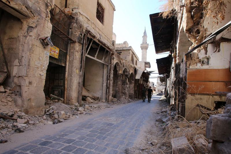 Syrian government soldiers walk in the damaged al-Farafira souk in the government-held side of Aleppo's historic city center on Sept. 16, 2016. (Youssef Karwashan/AFP/Getty Images)