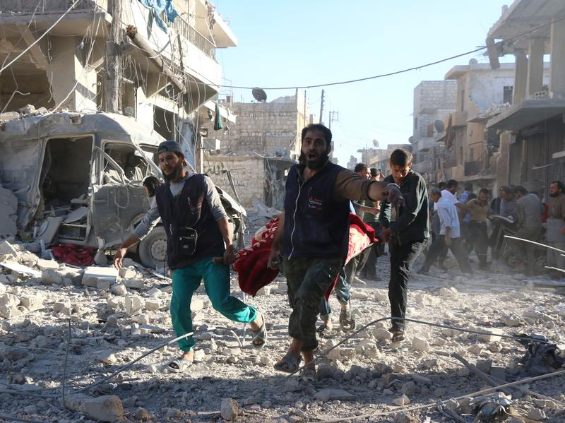 Syrian volunteers carry an injured person after pro-government forces struck the rebel-held neighborhood of Heluk in Aleppo Friday.