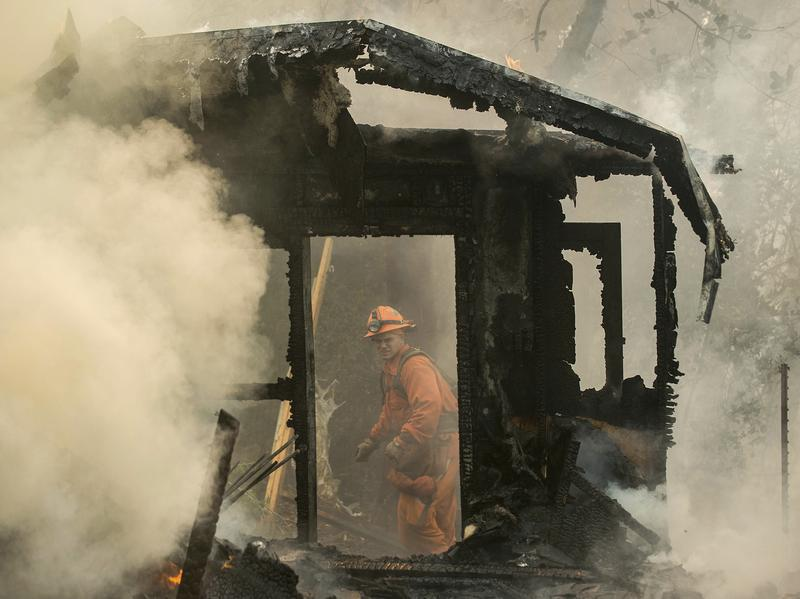 An inmate firefighter examines a burning structure while battling the Loma fire near Morgan Hill, Calif., on Wednesday.
