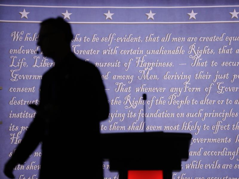 A producer walks past a lectern on the stage of the first presidential debate. The vice presidential debate is Monday night between Democrat Tim Kaine and Republican Mike Pence.