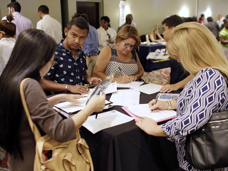 People fill out applications at a job fair in Miami Lakes, Fla., in July. The presidential candidates will be watching Friday's monthly Labor Department report for talking points on the unemployment rate and new jobs.