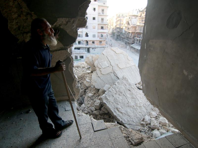 A 60-year-old local man who lost his two sons and his wife in airstrikes stands inside his collapsed home in Aleppo, Syria, on Monday.