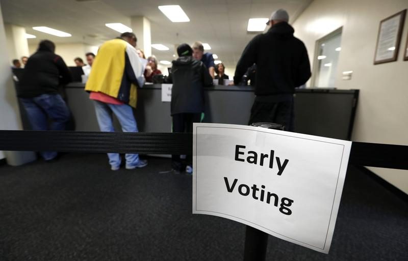 Local residents receive their ballots at the Polk County Election Office on the first day of early voting in Des Moines, Iowa, on Sept. 29, 2016. (Charlie Neibergall/AP)