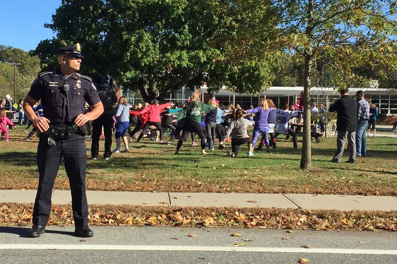 Parade attendees do yoga as a police officer looks on during a parade in support of wearing yoga pants Sunday in Barrington, R.I. (Courtesy Selena Maranjian)