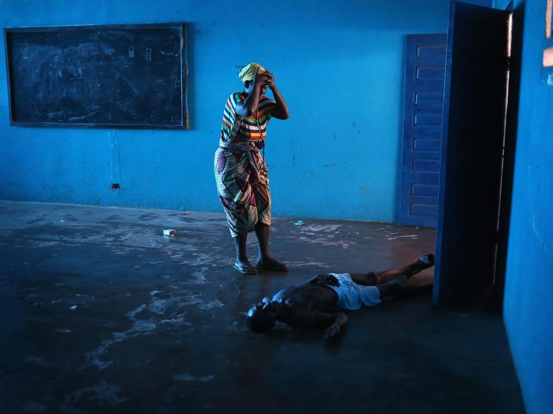 Omu Fahnbulleh stands over her husband after he staggered and fell, knocking him unconscious at an Ebola ward in Liberia in 2014.