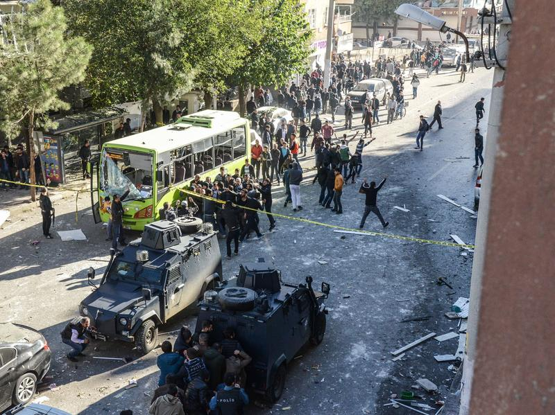 Turkish police officers take cover after the blast in the majority-Kurdish city of Diyarbakir on Friday. The car bomb was detonated hours after the government detained 12 pro-Kurdish legislators.