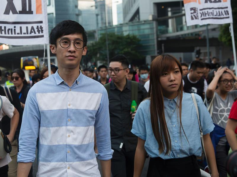 """Sixtus """"Baggio"""" Leung (left) and Yau Wai-ching (right) of the Youngspirations party march during a protest in Hong Kong on Sunday. Hong Kong police used pepper spray to drive back hundreds of protesters angry at China's decision to intervene in a row over whether the two pro-independence lawmakers should be barred from the city's legislature."""